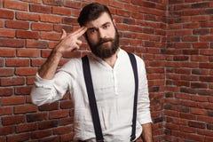 Den unga stiliga mannen som poserar att peka, fingrar på huvudet över tegelstenbakgrund Royaltyfria Bilder