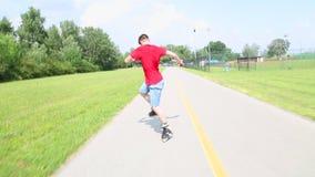 Den unga stiliga mannen som in rollerblading, parkerar på en härlig dag som gör några trick lager videofilmer