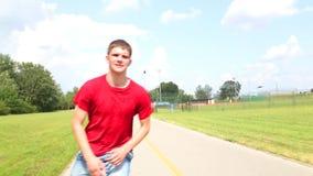 Den unga stiliga mannen som in rollerblading, parkerar på en härlig dag som omkring spelar lager videofilmer