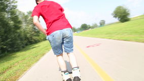 Den unga stiliga mannen som in rollerblading, parkerar på en härligt dag, slut och göra tillbaka lager videofilmer