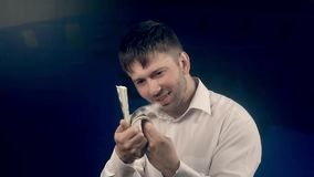 Den unga stiliga mannen som rymmer en packe av pengar, räknar hans dollar arkivfilmer