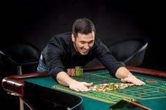 Den unga stiliga mannen som spelar rouletten, segrar på kasinot Arkivfoton