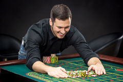 Den unga stiliga mannen som spelar rouletten, segrar på kasinot Royaltyfri Fotografi