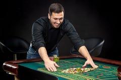 Den unga stiliga mannen som spelar rouletten, segrar på kasinot Royaltyfria Foton