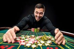 Den unga stiliga mannen som spelar rouletten, segrar på kasinot Fotografering för Bildbyråer