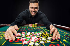 Den unga stiliga mannen som spelar rouletten, segrar på kasinot Royaltyfri Bild