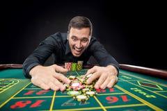 Den unga stiliga mannen som spelar rouletten, segrar på kasinot Arkivbild