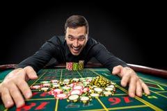 Den unga stiliga mannen som spelar rouletten, segrar på kasinot Royaltyfri Foto