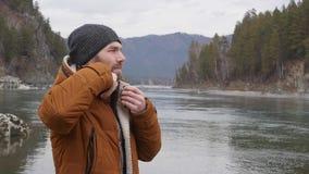 Den unga stiliga mannen står på banken av bergfloden i kallt väder långsam rörelse lager videofilmer