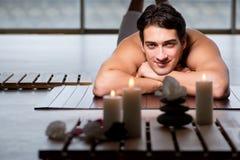 Den unga stiliga mannen under brunnsorttillvägagångssätt royaltyfri foto