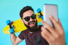 Den unga stiliga skäggiga hipstermannen gör selfie royaltyfria bilder