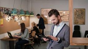 Den unga stiliga skäggiga mannen använder pekskärmminnestavlan i det moderna startup kontoret royaltyfri bild