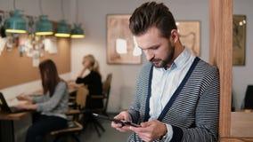Den unga stiliga skäggiga mannen använder pekskärmminnestavlan i det moderna startup kontoret arkivfoton