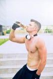 Den unga stolta mannen dricker aktiverande vatten efter mycket hård utbildning Fotografering för Bildbyråer