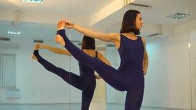 Den unga sträckta kvinnan som gör yoga, poserar och asanaen Härlig kvinna som inomhus tycker om yoga i sportkläder som in utarbet stock video