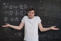 Den unga studenten gör matematikexamen och vet inte hur man löser svårt matematiskt problem arkivbild