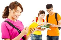 Den unga studenten läste en bok med klasskompisar arkivbilder