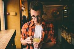 Den unga studenten sitter i restaurangen och smakar en varm drink man som dricker te på kafét Arkivfoton