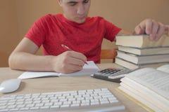 Den unga studenten skriver i anteckningsbok mellan böcker ung student som studerar kurser Royaltyfri Fotografi
