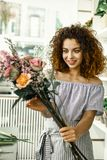 Den unga studenten som älskar hennes första jobb, medan arbeta i blom-, shoppar arkivfoton