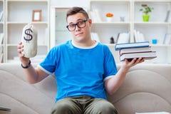Den unga studenten som förbereder sig för examina som hemma studerar på en soffa arkivfoton