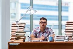 Den unga studenten som förbereder sig för högskolaexamina Arkivfoto