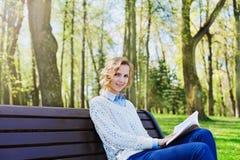 Den unga studentflickan i skjortasammanträde med en bok i hennes hand i en gräsplan parkerar, vetenskap och utbildning som läser Arkivbild