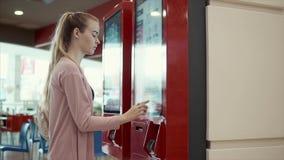 Den unga studentflickan väljer mat i snabbmatsrestaurang på den stora skärmen stock video