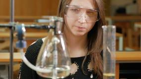 Den unga studentkvinnan som arbetar med kemikalieer och, skriver resultaten i universitet Säkerhetsexponeringsglas och ingen ämbe stock video