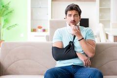 Den unga studentmannen med hals- och handskadasammanträde på soffan arkivfoton