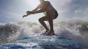 Den unga surfaren fångar en våg och löneförhöjningar till surfingbrädan i havet i Bali Pov-skott arkivfilmer
