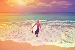 Den unga surfaren med ettbräde kommer från baksida havet, Bal Royaltyfri Foto
