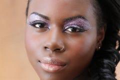 Den unga svarta kvinnan ser kameran Arkivfoto
