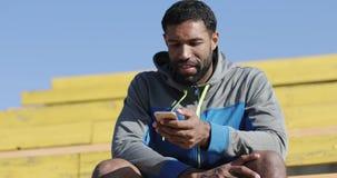 Den unga svarta mannen i träningsoverall skriver ett meddelande på en mobiltelefon arkivfilmer
