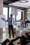 Den unga svarta mannen som framlägger ett kontorsmöte på, bläddrar diagrammet royaltyfri foto