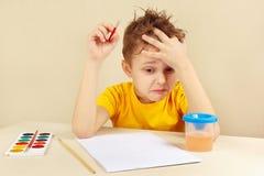 Den unga tankfulla konstnären i gul skjorta tänker vad för att måla Arkivfoto