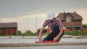 Den unga teknikern kontrollerar exaktheten av arbetet på konstruktionen av fundamentet Kontrollerar lutandevinkeln av Royaltyfri Fotografi