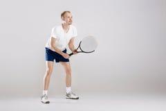 Den unga tennisspelaren spelar tennis på grå bakgrund arkivbild