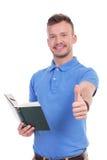 Den unga tillfälliga mannen med boken visar upp tummen Royaltyfri Bild