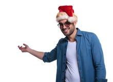 Den unga tillfälliga mannen i den santa hatten framlägger något Royaltyfri Fotografi
