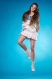 Den unga tonåriga flickan i en vit snör åt klänningbanhoppning Fotografering för Bildbyråer