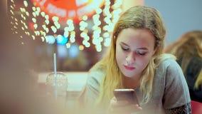 Den unga tonåriga flickan läste smartphonemeddelandet Hon har matställen i ett kafé Snabbmat afton, på bakgrunden av ljus arkivfilmer