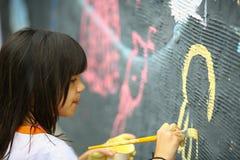 Den unga tonåriga flickan målar väggen Fotografering för Bildbyråer