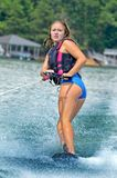 Den unga tonåriga flickan på ett trick skidar arkivfoton