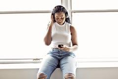 Den unga tonåriga härliga afrikansk amerikankvinnan tycker om att lyssna till musik med hörlurar arkivbilder