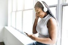 Den unga tonåriga härliga afrikansk amerikankvinnan tycker om att lyssna till musik med hörlurar arkivfoton