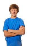 Den unga tonåriga pojken med armar korsade på vit royaltyfria bilder