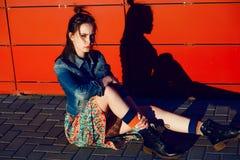 Den unga tonåringflickan som poserar och sitter nära stads- röd väggbakgrund i kjol, och jeans klår upp på solnedgången Fotografering för Bildbyråer