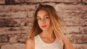 Den unga tonårs- flickan blir nära väggen, skakar hennes huvud, spelar med hår och ser kameran Vinden är stock video