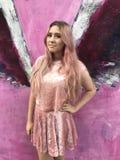 Den unga tonårs- flickan med långt blont hår och rosa färger klär Royaltyfria Foton